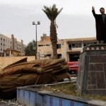 File photo of a man raising his hand as he stands on the spot where the statue of Hafez Al-Assad used to be in Raqqa province