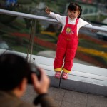 A girl poses for a photograph at a commercial area of downtown Shanghai