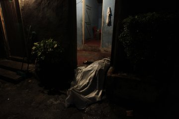 Covered-up body of man killed in shoot-out between members of Mara 18 street gang and police and military during anti-drug operation lies in house entrance in San Pedro Sula
