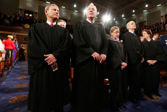 U.S. Supreme Court Chief Justice John Roberts stands with other justices prior to President Barack Obama's State of the Union speech on Capitol Hill in Washington