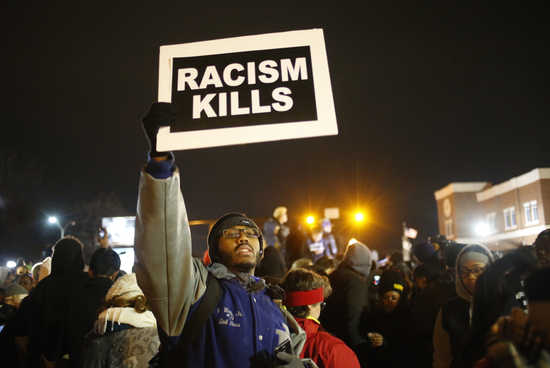 A protester holds a sign outside the Ferguson Police Department in Ferguson, Missour