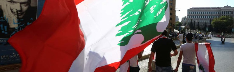 Lebanese anti-government protesters carry Lebanese flags as they walk towards the government building, background, during a demonstration against the trash crisis and government corruption, in downtown Beirut, Lebanon, Saturday, Aug. 29, 2015. Hundreds of people began gathering Saturday amid tight security in downtown Beirut, ahead of a major rally that is expected to be the largest of protests that began last week. The government's failure to resolve the crisis has evolved into wider protests against a political class that has dominated Lebanon since the end of the country's civil war in 1990. (AP Photo/Bilal Hussein)